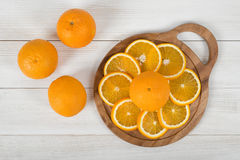Orange is cut into slices and well decorated on cutting board Stock Image