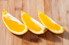Orange cuted into pieces. Some slices of oranges on chopping board Stock Images