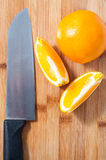 Orange cuted into pieces. Some slices of oranges on chopping board ,with a knife Royalty Free Stock Photography
