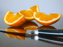 Orange Cuts. Pieces of an orange with a knife in the glass surface Stock Photography