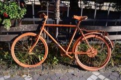 Orange cykel för gammal tappning som stöttas av ett trästaket royaltyfria bilder