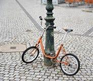 Orange cykel som kedjas fast till en pol Royaltyfri Foto