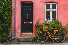 Orange cykel som lutas till den röda väggen i Köpenhamn arkivfoton