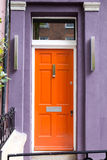 Orange dörr i det typiska London huset Arkivfoton