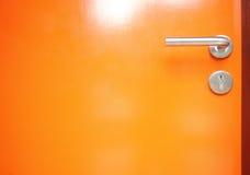 Orange dörr med metallhandtagdörren Royaltyfri Bild