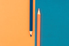 Orange and Dark Blue coloured pencils and paper Royalty Free Stock Photos