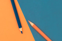 Orange and Dark Blue coloured pencils and paper Stock Photo