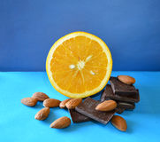 Orange, dark chocolate, almonds on blue surface and background Stock Image