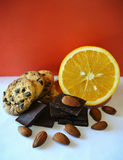 Orange, dark chocolate, almonds and cookies with chocolate chips on red background Royalty Free Stock Photography
