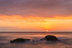Sunrise between two rocks on the coast of Tossa de Mar village royalty free stock images