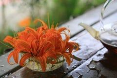 Orange Daylily-Blumen und Teekanne auf einer Tabelle stockfoto