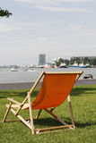 Orange deckchair in grass with view on busy river Royalty Free Stock Photography