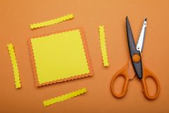 Orange and decorative scissor on pastel orange background. place. For your text on yellow paper Royalty Free Stock Photos