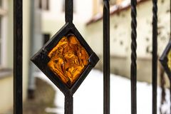 Orange decorative stained glass element in metal fence.  stock photography