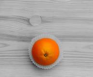 Orange in den kleinen Papierkörben auf der hölzernen Beschaffenheit Schwarzweiss Stockbild