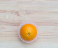 Orange in den kleinen Papierkörben auf hölzerner Beschaffenheit Stockbild