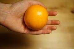 Orange in der Hand Stockbilder