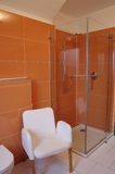 Orange Designer Bathroom. Modern bathroom with orange tiles, white appliances and a white chair Stock Photo