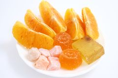 Orange dessert. Fruit jellies, marmalade, jujube and lobules of orange lie on a white dish Royalty Free Stock Images