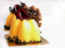 Orange dessert with edible red rose petal and chocolate decor stock image
