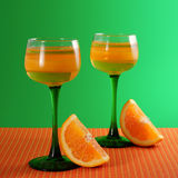 Orange dessert in a tall glass and slices of orange on a green background. Royalty Free Stock Photos