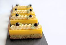 Orange desserts with green pistachio sponge and white chocolate cream royalty free stock images