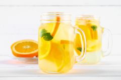 Orange detox water in mason jars on a white wooden table. Healthy food, drinks. stock photography