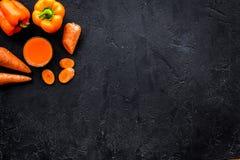 Orange detoxdryck med paprica och morot på svart copyspace för bästa sikt för bakgrund Arkivbilder
