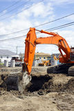 Orange digger and deep hole. Bright orange mechanical digger removing dirt to install sewage and water line for a new neighborhood in rural North America Royalty Free Stock Photography