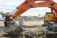 Orange digger and yellow dump truck Stock Photo