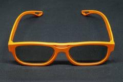 Orange 3D glasses. On a dark grey background royalty free stock photos