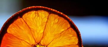 Orange disco show. Orange slice backlighted on dark blue background Royalty Free Stock Images