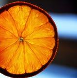 Orange disco show. Orange slice backlighted on dark blue background Royalty Free Stock Photography