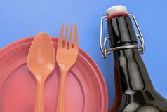 Orange dish and plastic cutlery next to a glass bottle stock photo