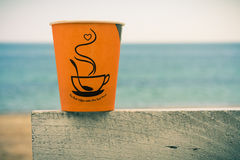 Orange disposable cup of coffee standing on a wooden fence Royalty Free Stock Photos