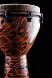 Orange Djembe conga  Drum. An orange colored Latin djembe conga drum isolated  against a black background in the vertical format with copy space Royalty Free Stock Photos