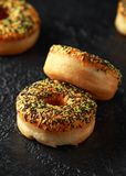 Orange Donut with sprinkles on rustic dark background stock photography