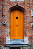 Orange door on the brick wall of the house in Bruges, Belgium Royalty Free Stock Photos