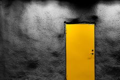 Orange door with dark grey wall with shadows and light. royalty free stock images