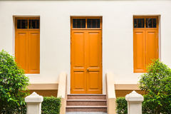 orange Door , orange window on Cream Wall on orange staircase wi Royalty Free Stock Photos