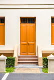 orange Door , orange window on Cream Wall on orange staircase wi Royalty Free Stock Images