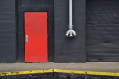 Orange Door, White Pipe, and Black Warehouse Wall, Portland, Oregon. Here is an orange door and white pipe with 3 fire hose outlets on a yellow-lined loading stock photography