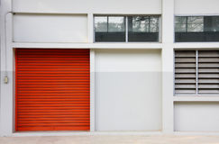 Orange door on the white wall. Structure of orange metal door on the white wall stock photo