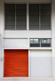 Orange door on the white wall. Structure of orange metal door on the white wall stock image