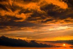 Orange dramatic cartoon cumulus clouds at sunset