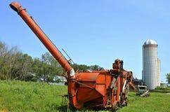 Orange Dreschmaschine auf amischem Bauernhof Stockfotografie