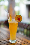 Orange drink. Cold orange drink with a cherry on the side of the glass Royalty Free Stock Photography