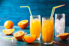 Orange drink. Fresh orange juice in glasses, cubes of ice and slice of fruits  on blue table. Healthy vitamin drink Stock Image