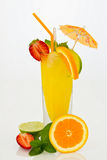 Orange drink in a highball glass with fresh fruits. Refreshing orange drink in a highball glass with fresh orange, strawberry, lime, straw and umbrella Stock Images