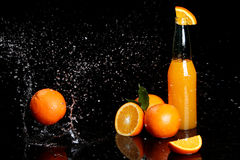 Orange drink and huge splashes Stock Photos